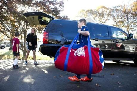 Liam Heney, 8, lugs an equipment bag to the car as mom Kelly and brother Cormac get ready for a day of nonstop sports.
